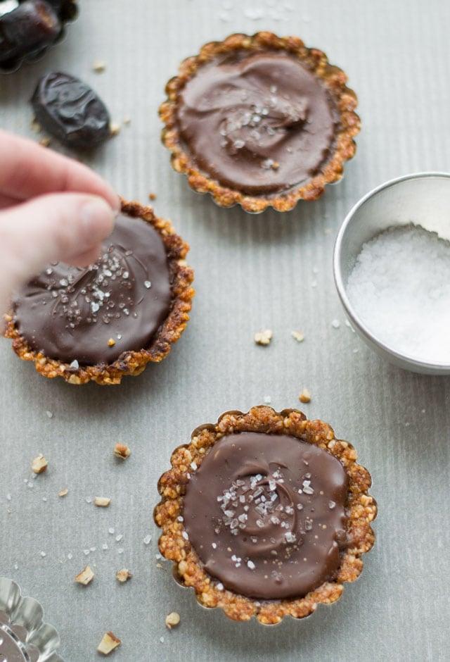 Glutenvrije mini taartjes met chocolade, karamel van dadels en een bodem van noten. Met een klein beetje zeezout is het een heerlijke, glutenvrije traktatie.