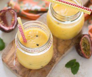 Twee glazen tropische smoothie met mango en passievrucht