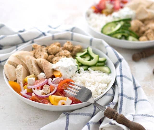 Griekse kip, komkommer, salade, pita en tzatziki in een bowl