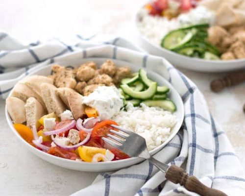 Buddha bowl met Griekse kip, komkommer, salade, pita en tzatziki