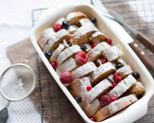 Een foto van Wentelteefjes uit de oven met rood fruit en poedersuiker
